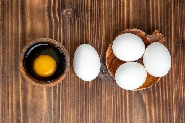 Vue de dessus des oeufs crus entiers sur la surface en bois brun repas repas petit déjeuner en bois