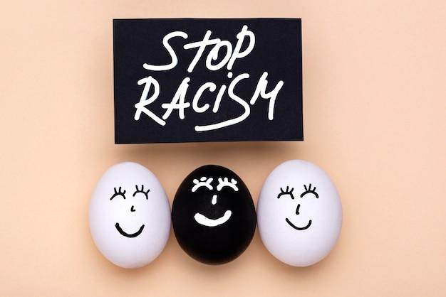 Vue de dessus des œufs de différentes couleurs avec des visages pour les vies noires, le mouvement est important avec stop racisme