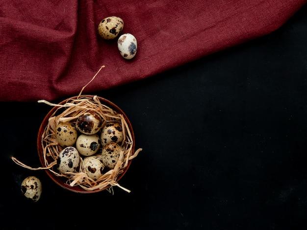 Vue de dessus des œufs avec nid dans un bol sur fond bordeaux et noir avec copie espace