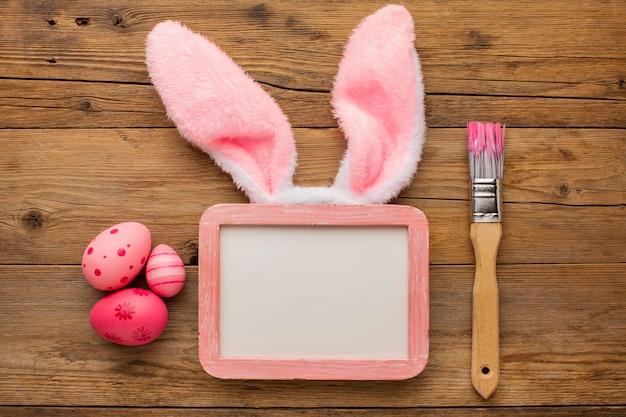 Vue de dessus des oeufs de pâques colorés avec cadre et pinceau à côté des oreilles de lapin