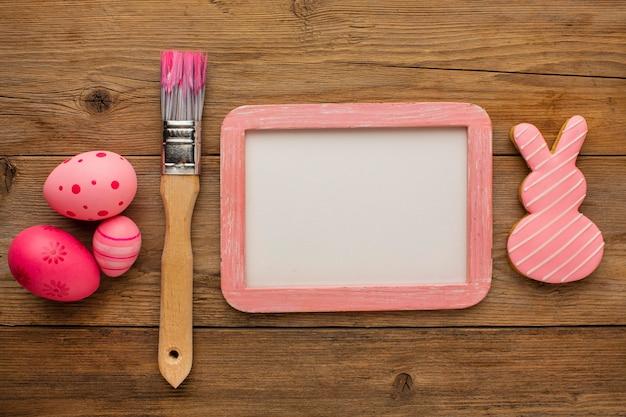 Vue de dessus des oeufs de pâques colorés avec cadre et pinceau
