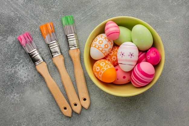 Vue de dessus des oeufs de pâques colorés dans un bol avec des pinceaux