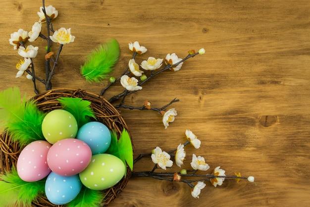 Vue de dessus d'un oeufs de pâques colorés dans le nid, des plumes vertes et des fleurs de printemps sur fond de bois brun avec espace de message