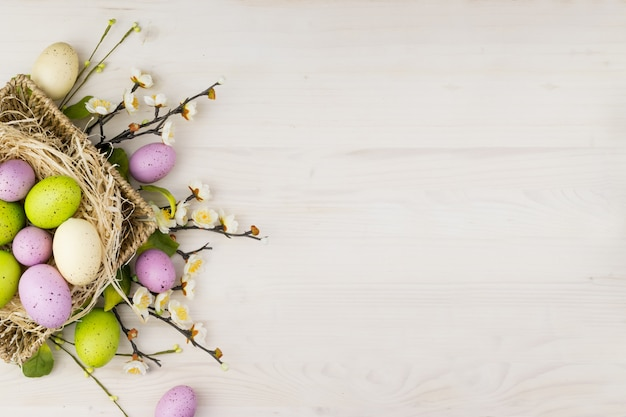 Vue de dessus d'un oeufs de pâques colorés dans un panier et des fleurs de printemps sur un fond en bois clair avec espace de message.
