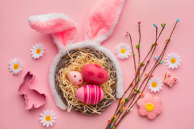 Vue de dessus des oeufs de pâques colorés dans le panier avec des oreilles de lapin et des fleurs de camomille