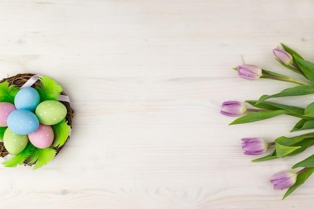 Vue de dessus d'un oeufs de pâques colorés dans un panier avec des plumes vertes et des tulipes violettes sur un fond en bois clair avec un espace de message.