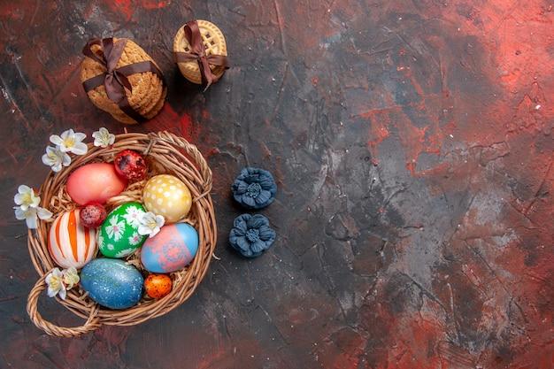Vue de dessus des oeufs de pâques colorés à l'intérieur du panier avec des biscuits sur une surface sombre