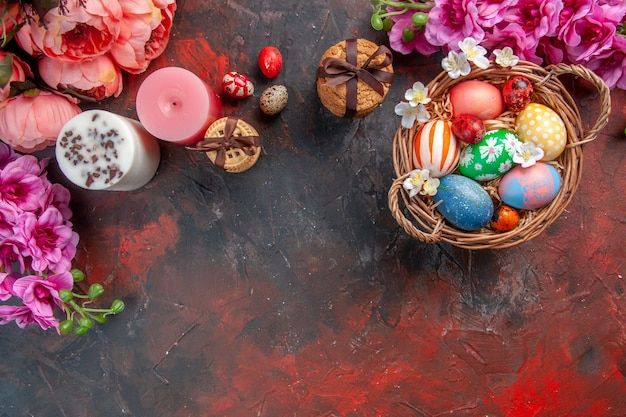 Vue de dessus des oeufs de pâques colorés à l'intérieur du panier avec des fleurs et des biscuits sur une surface sombre