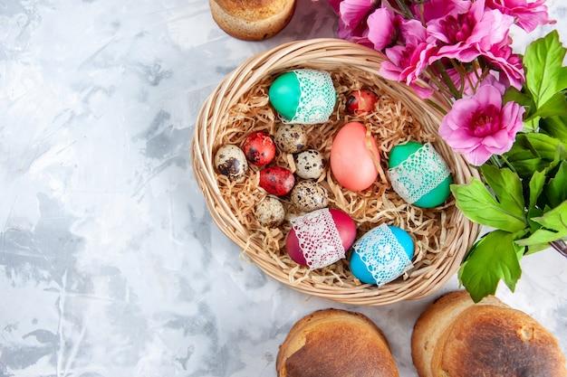 Vue de dessus des oeufs de pâques colorés à l'intérieur du panier avec des fleurs et des bougies sur une surface blanche