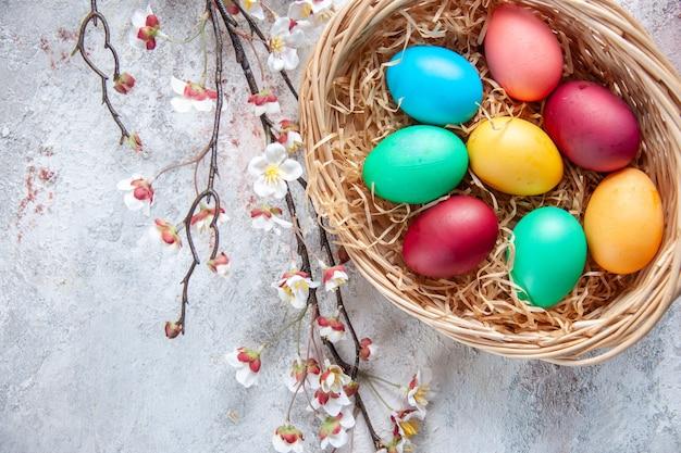 Vue de dessus des oeufs de pâques colorés à l'intérieur du panier avec des fleurs sur une surface blanche