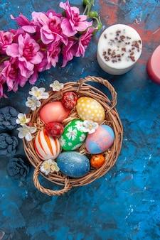 Vue de dessus des oeufs de pâques colorés à l'intérieur du panier avec des fleurs sur une surface bleue