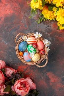 Vue de dessus des oeufs de pâques colorés à l'intérieur du panier avec des fleurs sur une surface sombre