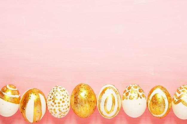 Vue de dessus des oeufs de pâques colorés avec de la peinture dorée dans différents motifs. espace de copie.
