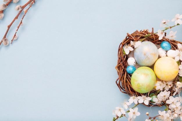 Vue de dessus des oeufs de pâques dans le nid et le saule sur fond bleu avec des fleurs en fleurs. copiez l'espace pour le texte.
