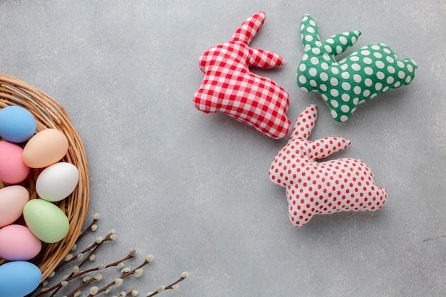 Vue de dessus des oeufs de pâques multicolores avec des décorations en forme de lapin