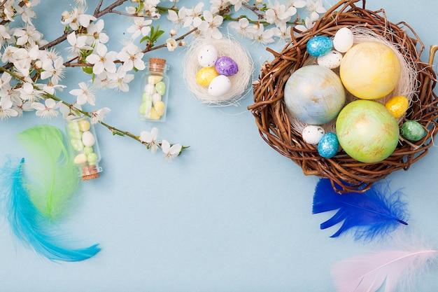 Vue de dessus des oeufs de pâques en nid et des bouteilles en verre sur un fond bleu avec des fleurs en fleurs copiez l'espace pour le texte.