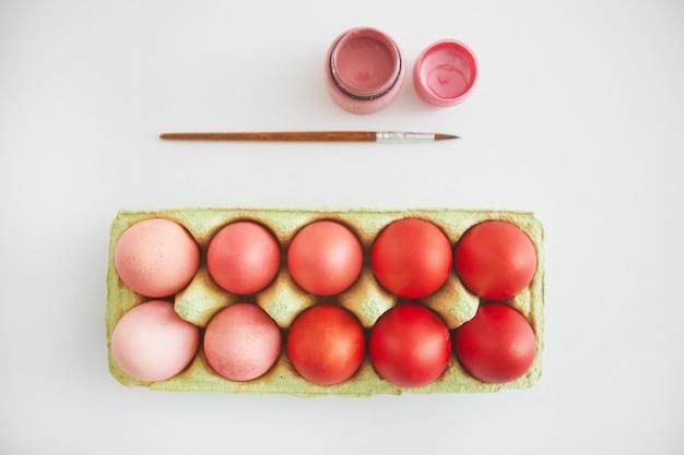 Vue de dessus des oeufs de pâques rose et rouge pastel en caisse disposés en composition minimale avec pinceau sur fond blanc, espace copie