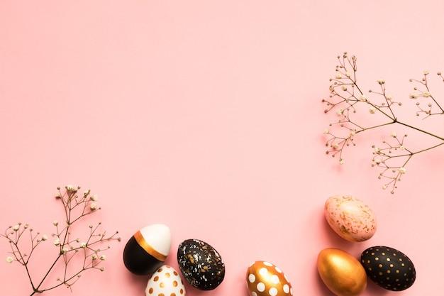 Vue de dessus des oeufs peints en bois dans les couleurs or, noir et rose avec branche de gypsophile sur fond rose. fond de joyeuses pâques avec espace copie
