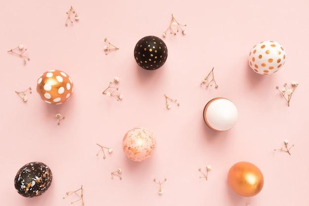 Vue de dessus des oeufs peints en bois dans les couleurs or, noir et rose avec une branche de gypsophile sur fond rose. joyeux fond de pâques