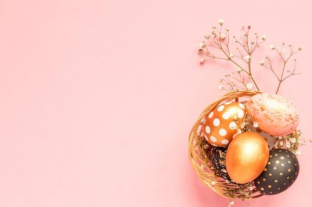 Vue de dessus des oeufs peints en bois dans les couleurs or, noir et rose dans un panier en osier avec une branche de gypsophile sur fond rose.