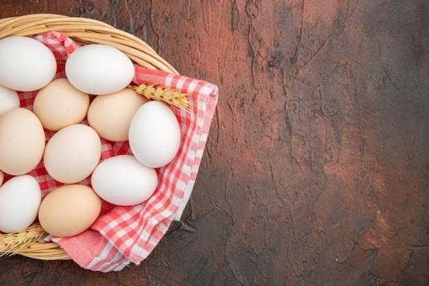 Vue de dessus des œufs de poule blancs à l'intérieur du panier avec une serviette sur la table sombre