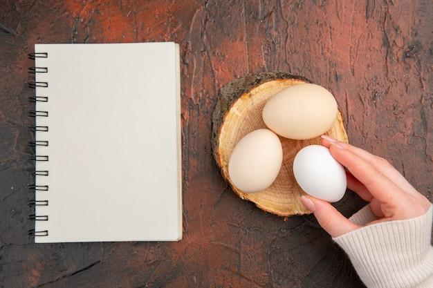 Vue de dessus des œufs de poule blancs sur un repas de table sombre couleur animale photo brute petit-déjeuner à la ferme