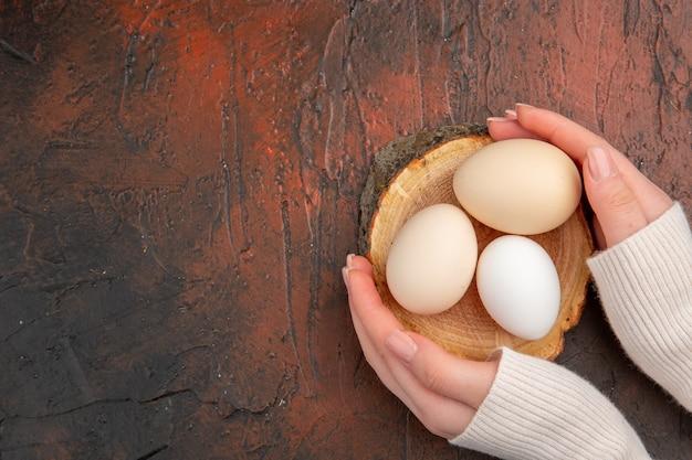 Vue de dessus des œufs de poule blancs sur un repas de table sombre photo de couleur animale petit-déjeuner de nourriture de ferme