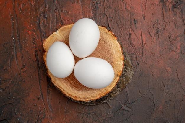 Vue de dessus des œufs de poule blancs sur une table sombre repas d'animaux photo couleur ferme brute
