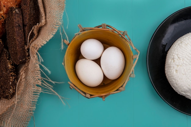 Vue de dessus des œufs de poule dans un panier avec du fromage et du pain noir sur fond turquoise
