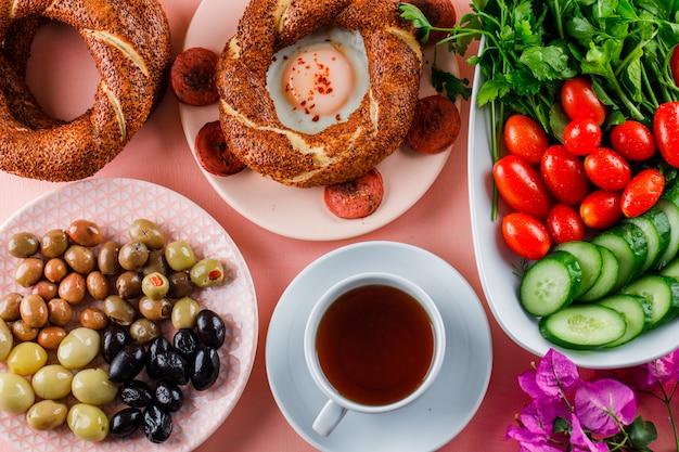 Vue de dessus des œufs avec des saucisses dans une assiette avec une tasse de thé, bagel turc, olive, salade sur une surface blanche