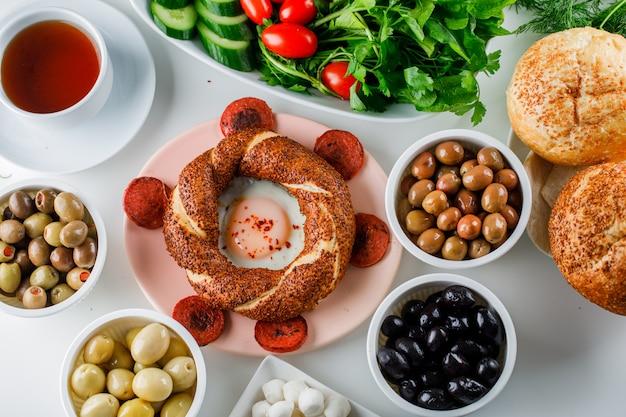 Vue de dessus des œufs avec des saucisses dans une assiette avec une tasse de thé, bagel turc, salade sur une surface blanche