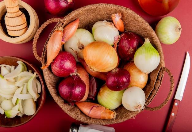 Vue de dessus des oignons dans le panier avec du poivre noir, des oignons tranchés dans un bol, du sel, du beurre et un couteau autour de la surface rouge