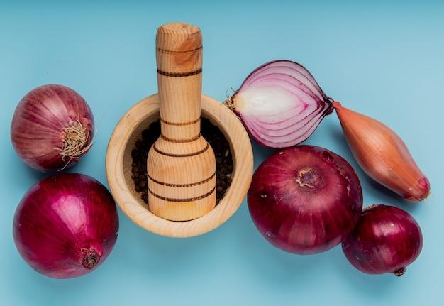 Vue de dessus des oignons entiers et coupés et des graines de poivre noir dans un broyeur d'ail sur une surface bleue
