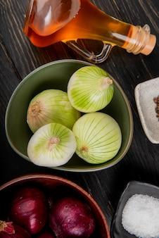 Vue de dessus des oignons rouges et blancs dans des bols sel fondu beurre poivre noir sur table en bois