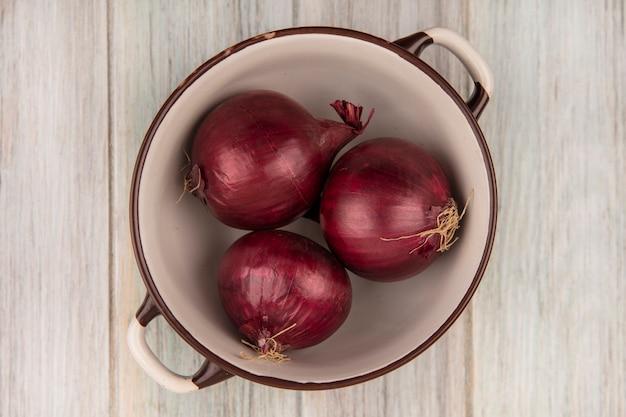 Vue de dessus des oignons rouges sains et frais sur un bol sur un mur en bois gris
