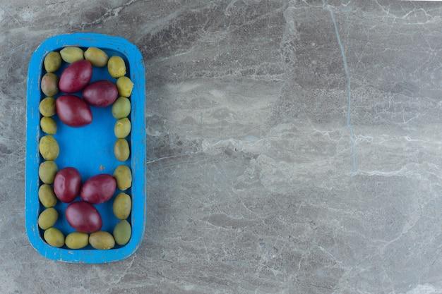 Vue de dessus des olives marinées avec des palmiers sur une plaque en bois bleue.