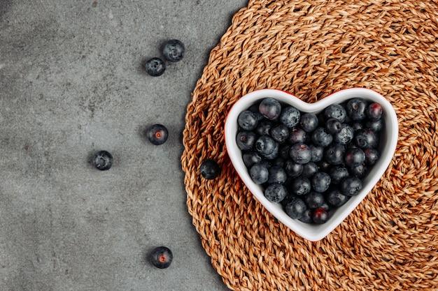 Vue de dessus des olives noires dans un bol en forme de coeur sur un dessous de plat en rotin et fond gris. horizontal