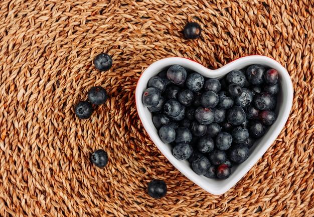 Vue de dessus des olives noires dans un bol en forme de coeur sur fond de rotin. horizontal