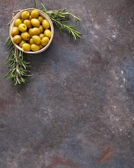 Vue de dessus des olives vertes dans un bol avec du romarin.