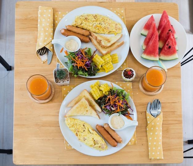 Vue de dessus d'omelette au jus d'orange, melon d'eau, croissants, céréales et fruits sur une table en bois.