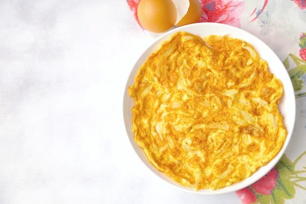 Vue de dessus de l'omelette (omelette) avec oignon servi sur plaque blanche. ingrédient frais. végétarien. nourriture nature morte. populaire en thaïlande. copiez l'espace.
