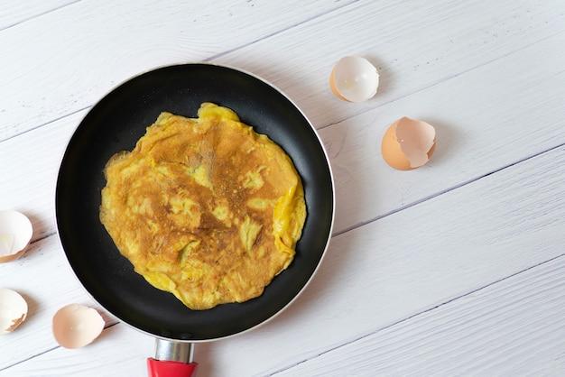 Vue de dessus omelette thaïlandaise ou œuf frit peu brûlé sur une poêle noire