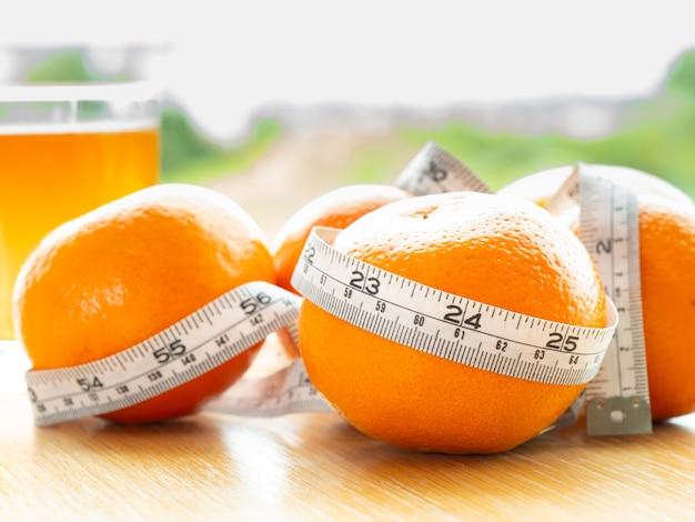 Vue de dessus de l'orange, citron, ruban à mesurer illustrent au produit naturel pour le régime de perte de poids
