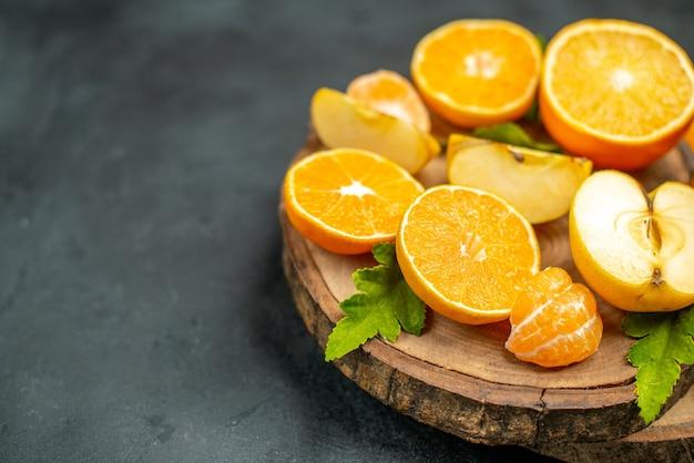 Vue de dessus des oranges coupées et des pommes coupées en orange sur fond sombre