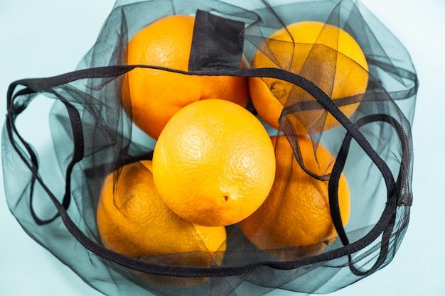 Vue de dessus des oranges dans un sac à cordes réutilisable.