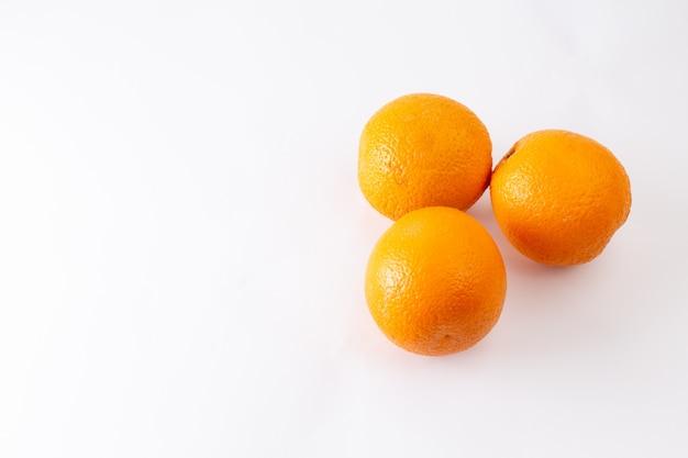 Vue de dessus des oranges entières fraîches juteuses et aigres sur le fond blanc fruits exotiques de couleur agrumes