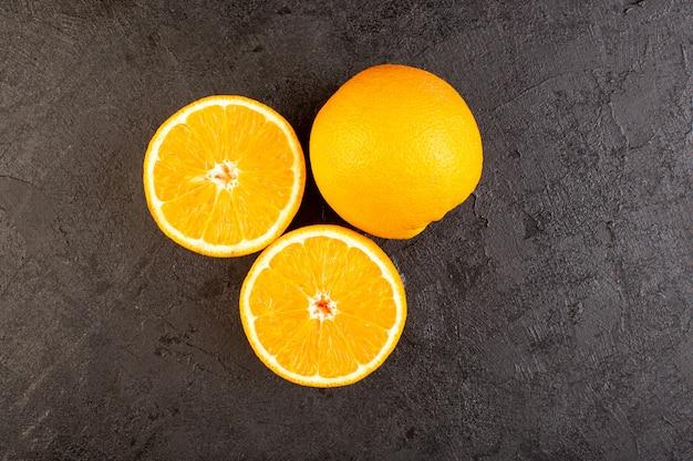 Une vue de dessus des oranges fraîches aigres mûres entières et coupées en tranches d'agrumes tropicaux jaune vitamine tropicale sur le bureau sombre