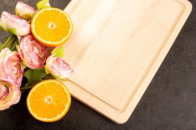 Une vue de dessus des oranges fraîches aigres mûres entières et tranchées de roses séchées moelleuses agrumes tropical vitamine jaune sur le bureau sombre