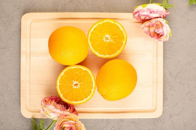 Une vue de dessus des oranges fraîches aigres mûres tranchées et des agrumes moelleux et juteux de la vitamine tropicale jaune sur la crème