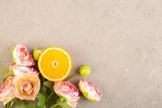Une vue de dessus des oranges fraîches aigres mûres tranchées et entières d'agrumes tropicaux jaune vitamine tropicale sur le bureau de la crème
